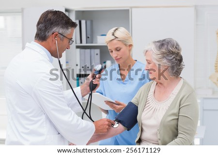 Doctor checking senior patients blood pressure while nurse noting it in clinic - stock photo