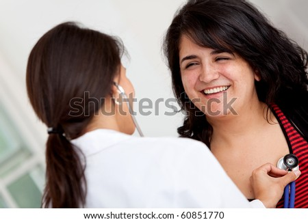 Doctor checking the heart of a patient with a stethoscope - stock photo