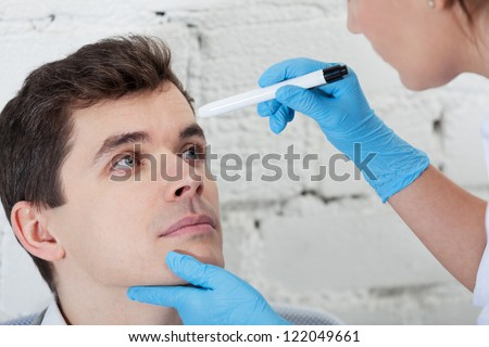 Doctor checking tired eyes of patient - stock photo