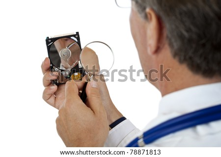 Doctor checks computer hard disk with magnifying glass.Isolated on white background.