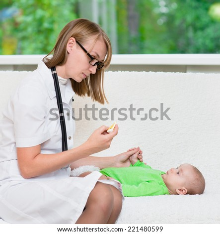 doctor checks the temperature of baby  - stock photo