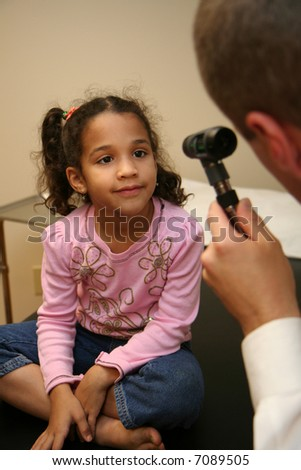 Doctor checks young child in an exam room - stock photo