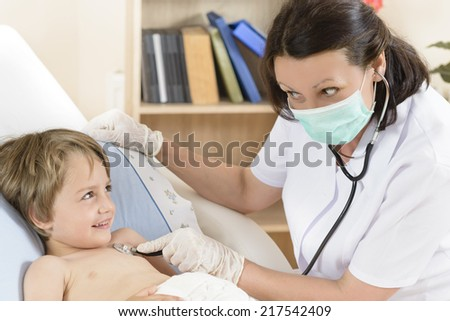 Doctor consulting a cute funny boy - stock photo