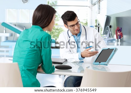 Doctor consulting with female patient, presenting results on tablet computer, sitting at desk.