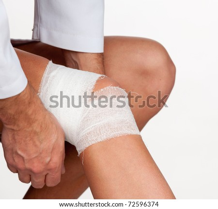 Doctor cover the knee of patient by bandage isolated on a white background - stock photo