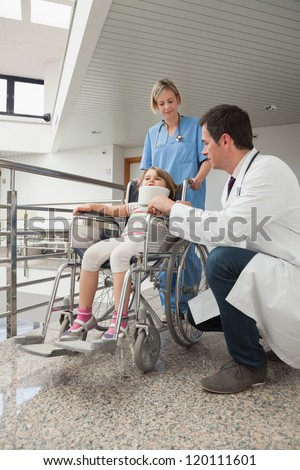 Doctor crouching next to child in wheelchair with neck brace with nurse pushing it - stock photo