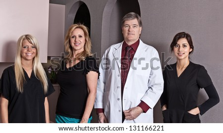 Doctor/dentist and his office staff pose for a picture.