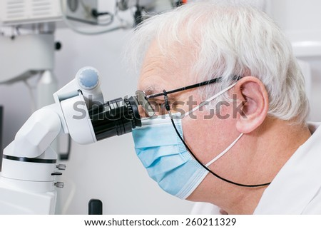 Doctor dentist using dental microscope in modern dental office