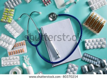 doctor desk workplace stethoscope spiral notebook blank copyspace - stock photo