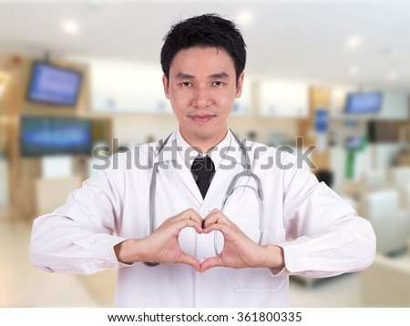 doctor doing a heart with his hands in hospital - stock photo