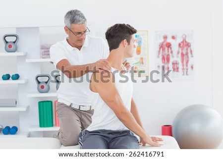 Doctor doing back adjustment in medical office - stock photo
