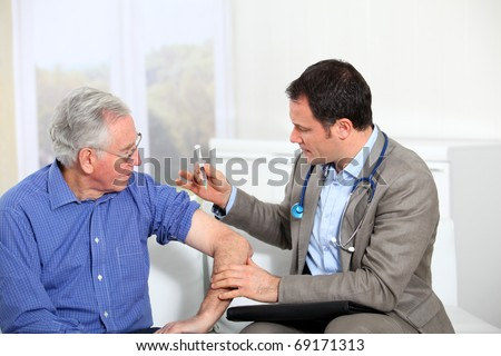 Doctor doing vaccination to elderly man - stock photo