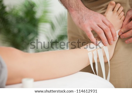 Doctor dressing an ankle in a room - stock photo