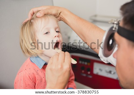 Doctor ENT checking ear with otoscope to girl patient  - stock photo