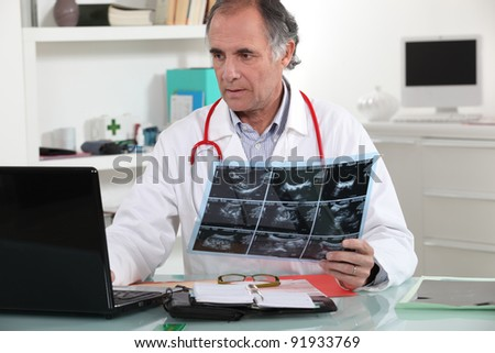 Doctor entering x-ray results into his database - stock photo