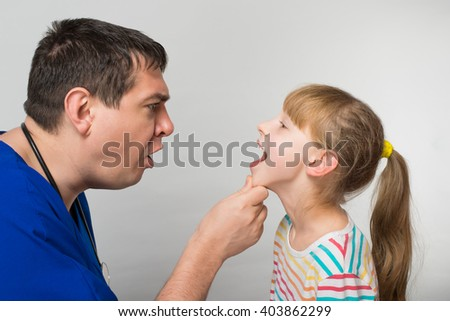 Doctor examines a child's throat - stock photo