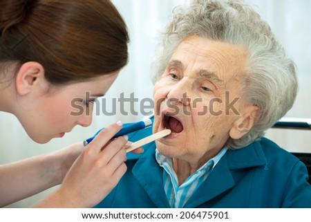 Doctor examines elderly woman for sore throat - stock photo