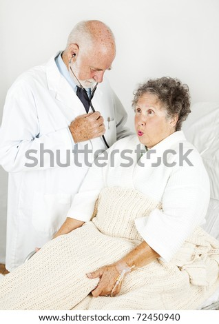 Doctor examines his elderly female patient in the hospital. - stock photo