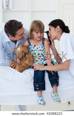 Doctor examing littl girl's ears during a visit - stock photo