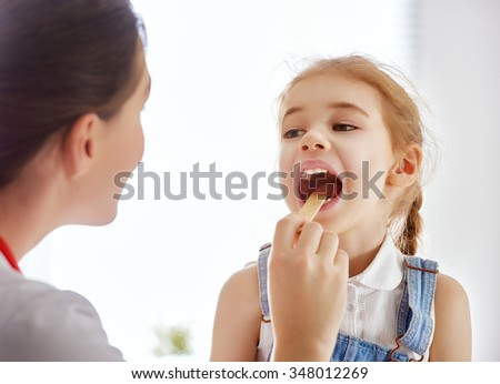 doctor examining a child girl in a hospital - stock photo