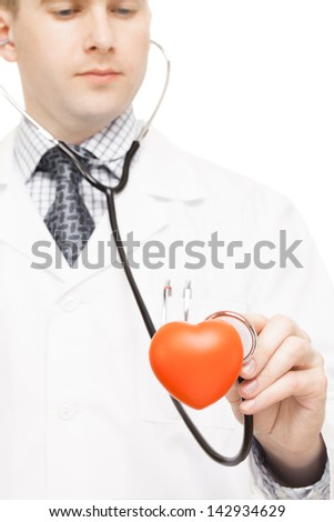 Doctor examining a heart toy with stethoscope on white background - stock photo