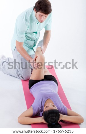 Doctor examining a patient leg at physiotherapy center - stock photo