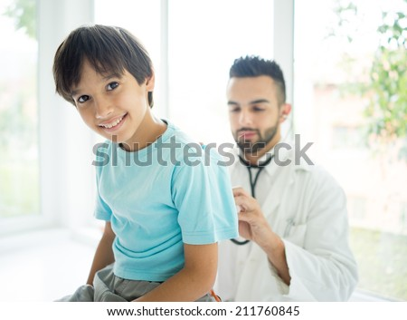 Doctor examining a school boy at hospital - stock photo
