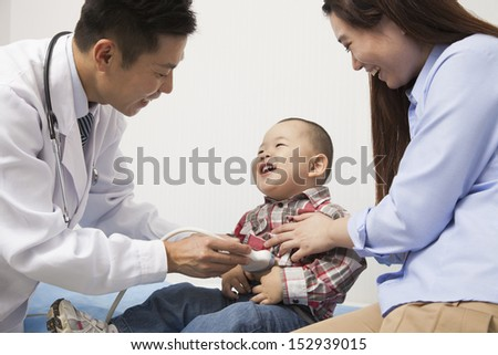 Doctor Examining Baby Boy In Office - stock photo