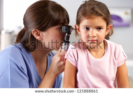 Doctor Examining Child's Ears In Doctor's Office - stock photo
