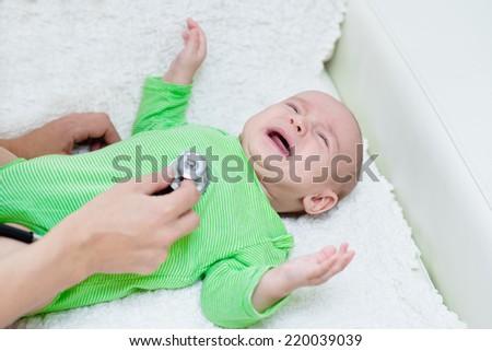 doctor examining crying baby with stethoscope - stock photo