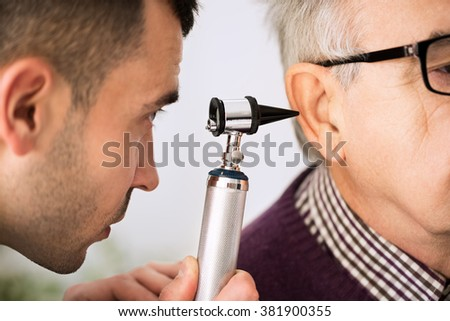 Doctor Examining Ear of a old patient, close up - stock photo