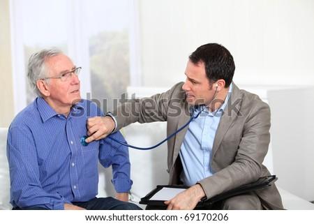 Doctor examining elderly man's health - stock photo