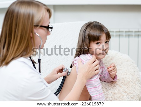 doctor examining girl with stethoscope - stock photo