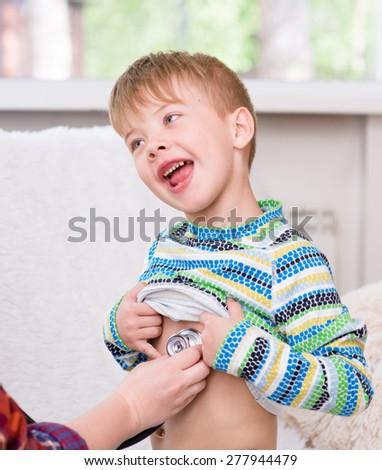 doctor examining happy boy with stethoscope - stock photo