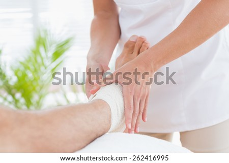 Doctor examining her patient ankle in medical office