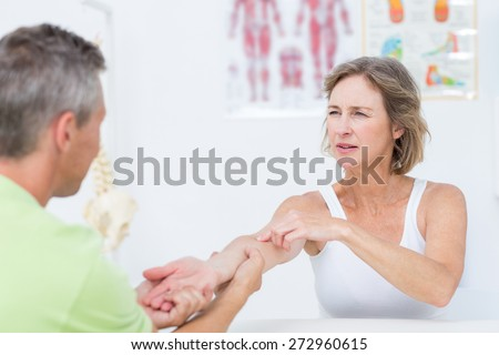 Doctor examining his patients arm in medical office - stock photo