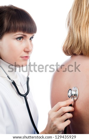 Doctor examining lungs of a female patient with stethoscope - stock photo