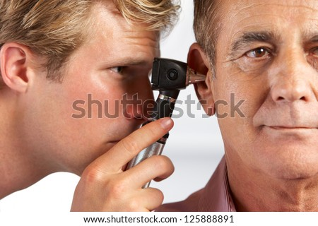 Doctor Examining Male Patient's Ears - stock photo