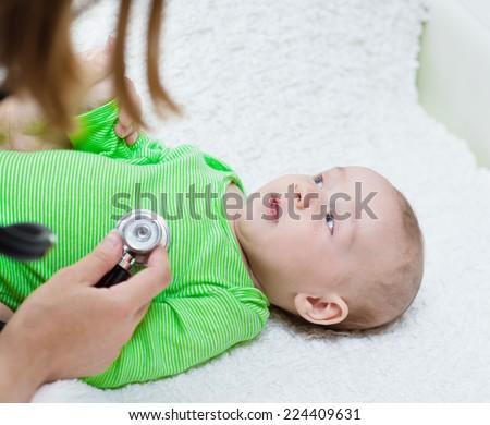 doctor examining newborn baby with stethoscope - stock photo