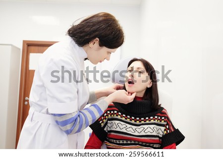 Doctor examining patients painful throat - stock photo