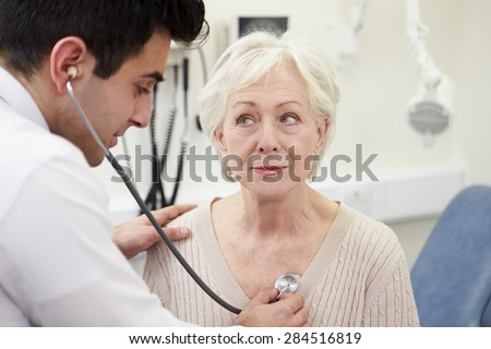 Doctor Examining Senior Female Patient In Hospital - stock photo