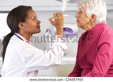 Doctor Examining Senior Female Patient's Eyes - stock photo