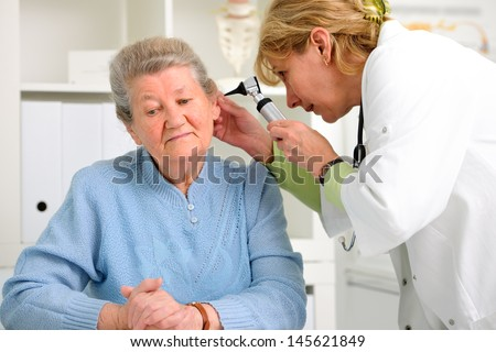 doctor examining senior patient's ears - stock photo