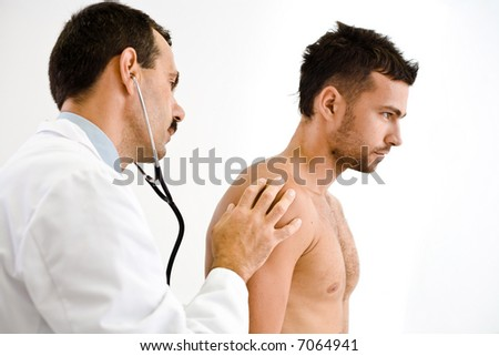 Doctor examining young male patient. - stock photo