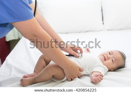 Doctor exams Asian newborn baby with stethoscope in the hospital