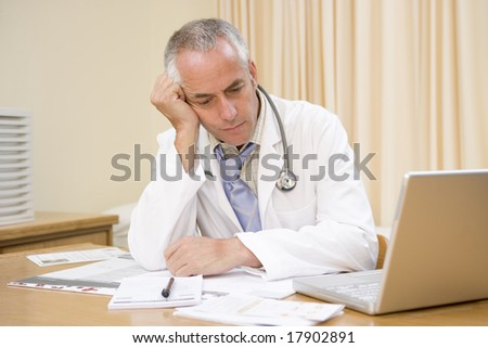 Doctor exhausted at desk - stock photo