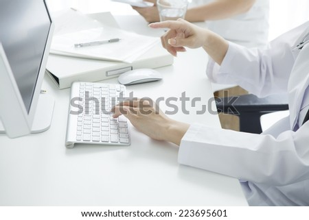 Doctor explained while looking at the computer monitor - stock photo