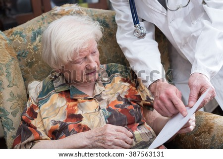 Doctor explaining a prescription to an old woman at home - stock photo