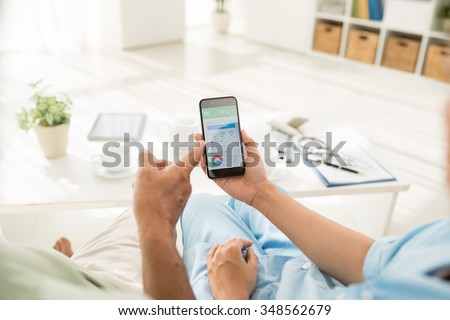 Doctor explaining aged patient how to use calorie counter on the smartphone - stock photo