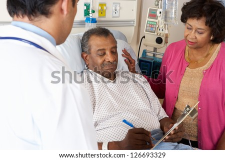 Doctor Explaining Consent Form To Senior Patient - stock photo